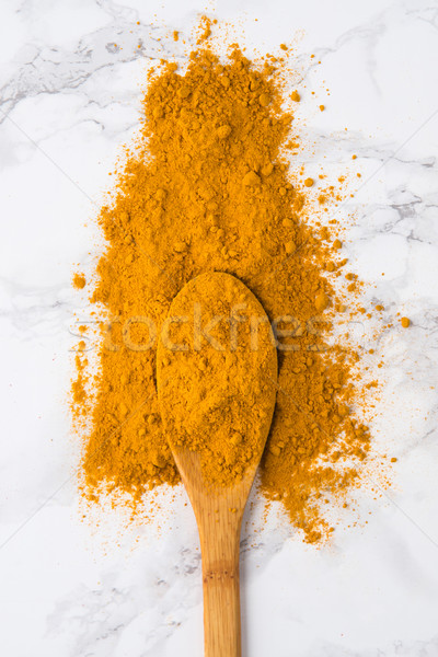 Top view of a wooden spoon with turmeric powder Stock photo © deandrobot