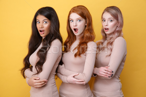 Three shocked ladies with crossed arms posing in studio Stock photo © deandrobot