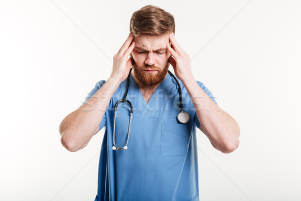 Portrait of a tired male medic suffering from a headache Stock photo © deandrobot