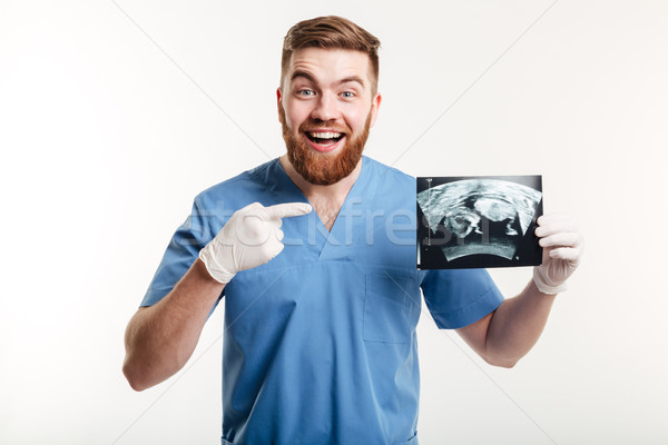 Happy excited male medical doctor or nurse pointing finger Stock photo © deandrobot
