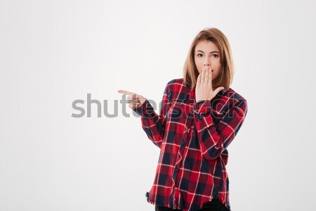 Surprised smiling woman pointing away Stock photo © deandrobot