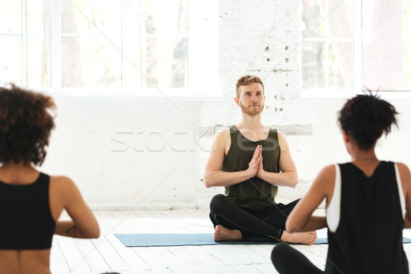 Group of women with male instructor sitting on yoga mats Stock photo © deandrobot