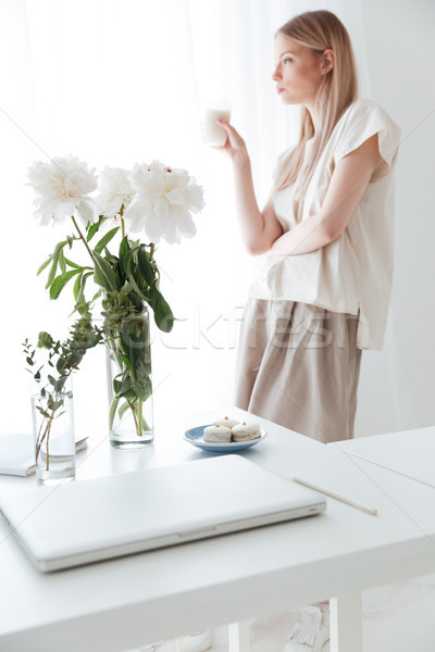 Serious woman standing near window indoors drinking coffee. Stock photo © deandrobot