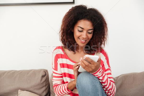 молодые африканских женщину диван смартфон Сток-фото © deandrobot
