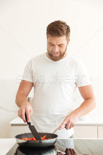 Vertical image of smiling bearded man cooking vegetables Stock photo © deandrobot