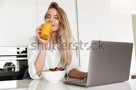 Displeased young woman using laptop in kitchen Stock photo © deandrobot