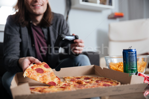 Young man gamer play games with joystick while eating. Stock photo © deandrobot