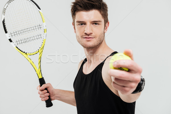 Handsome young sportsman holding tennis ball and racket Stock photo © deandrobot