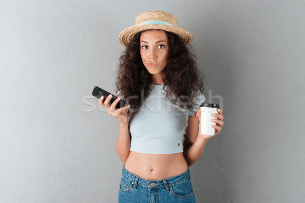 Pretty curly woman in hat with coffee and smartphone Stock photo © deandrobot
