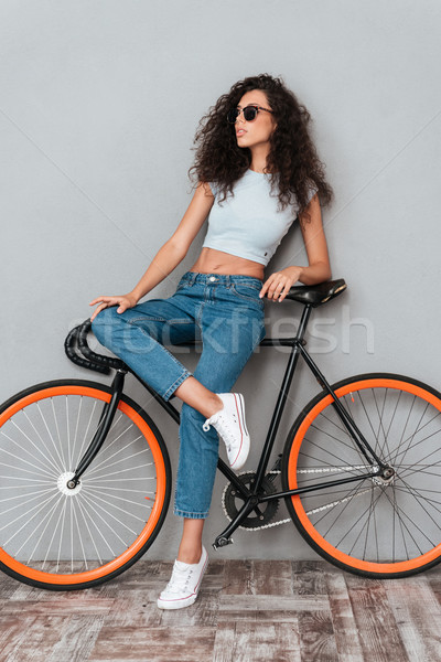 Full length picture of pretty curly woman in sunglasses Stock photo © deandrobot