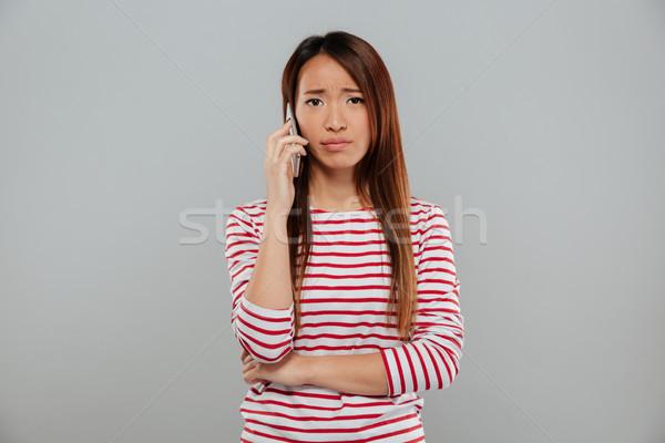 Confusi giovani asian donna parlando telefono Foto d'archivio © deandrobot