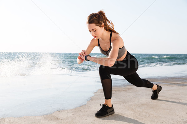 Portrait of young healthy sport woman checking time while doing  Stock photo © deandrobot