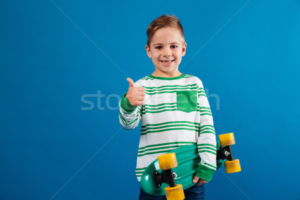 Smiling young boy holding skateboard and showing thumb up Stock photo © deandrobot