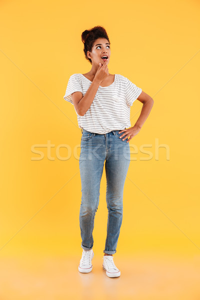Full-length image of surprised lady looking up at copy space isolated over yellow Stock photo © deandrobot