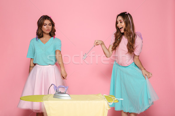 Portrait of a two funny young girls ironing clothes Stock photo © deandrobot