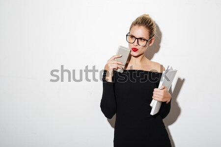 Mystery business woman in dress and eyeglasses holding documents Stock photo © deandrobot