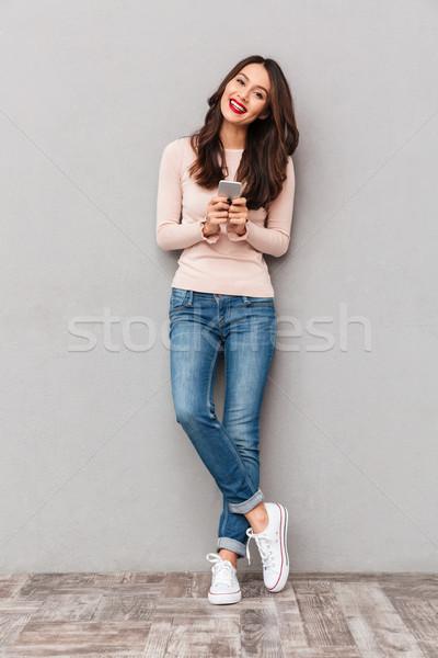 фото красивой женщины кроссовки джинсов Сток-фото © deandrobot