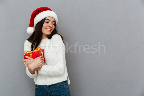 Portrait of a pretty smiling girl wearing red santa hat Stock photo © deandrobot