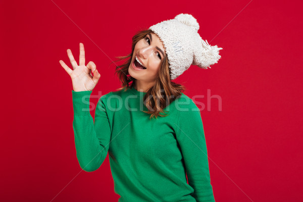 Happy brunette woman in sweater and funny hat showing ok Stock photo © deandrobot