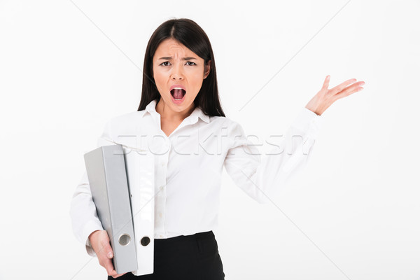 Portrait of a furious asian businesswoman holding binders Stock photo © deandrobot