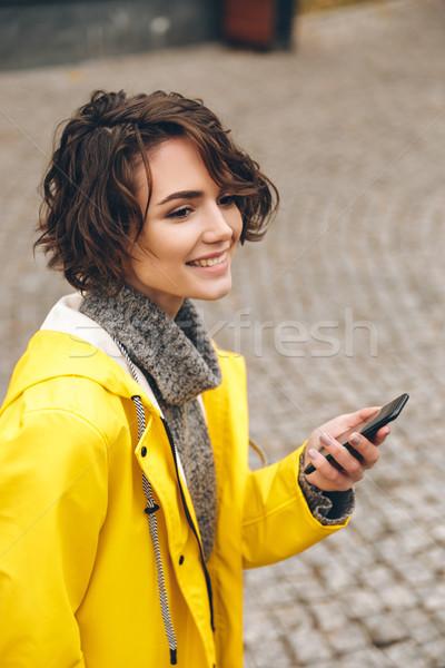 Portrait of beautiful brunette female walking on paving stones h Stock photo © deandrobot