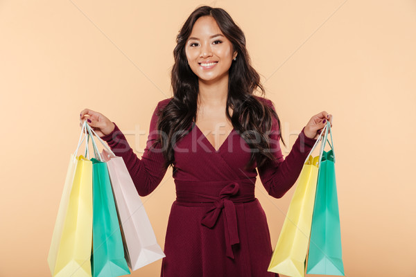 Shot of pleased asian female in pretty maroon dress posing over  Stock photo © deandrobot