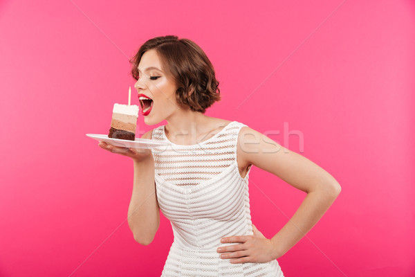 Portrait of a young girl eating a piece of cake Stock photo © deandrobot