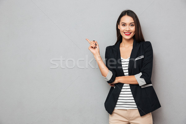 Stock photo: Smiling asian business woman pointing up and looking at camera