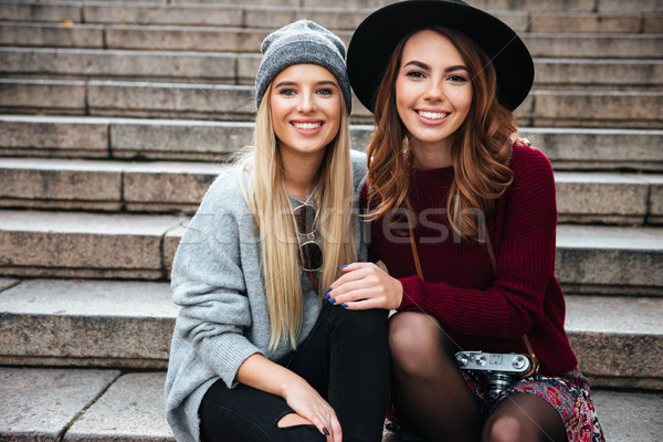 Portrait of two smiling cheerful girls sitting on a staircase Stock photo © deandrobot