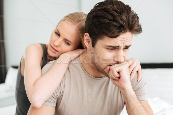 Pretty woman comfort her sad man while they sitting in bed Stock photo © deandrobot