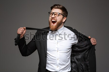 Portrait of a crazy young businessman dressed in suit Stock photo © deandrobot