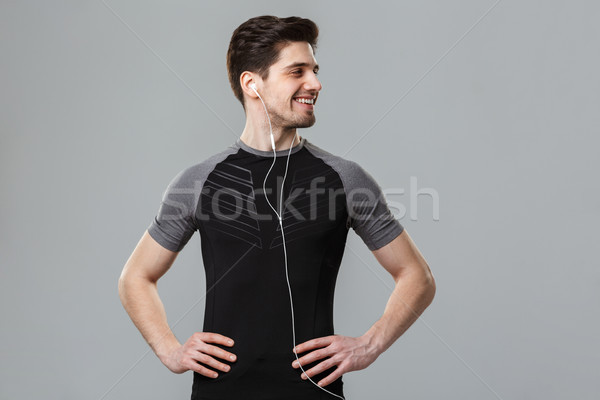 Cheerful young sportsman listening music with earphones. Stock photo © deandrobot