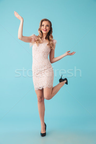 Full length image of Cheerful blonde woman in dress posing Stock photo © deandrobot