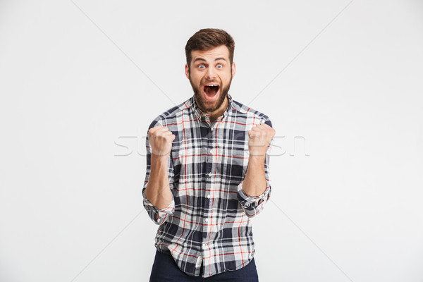 Portrait of an excited young man in plaid shirt Stock photo © deandrobot