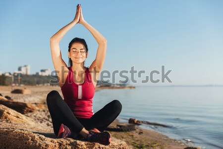 Smiling young sportswoman sitting in yoga position Stock photo © deandrobot