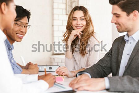 Smiling young businesswoman sitting at the table Stock photo © deandrobot