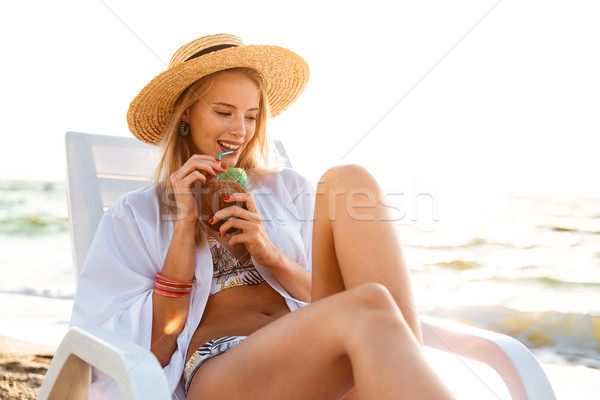 Image of gorgeous caucasian woman 20s in straw hat drinking swee Stock photo © deandrobot