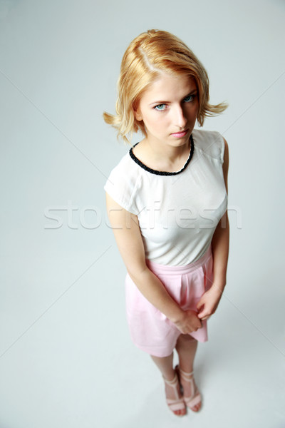 Compassionate young girl standing on gray background Stock photo © deandrobot