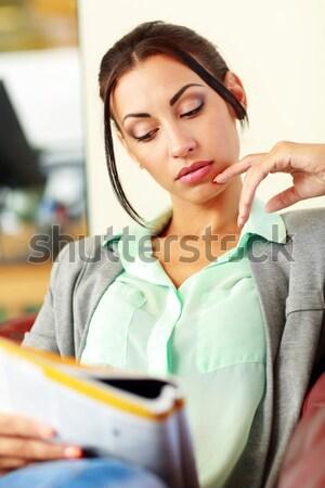 Businesswoman reading magazine in modern office Stock photo © deandrobot
