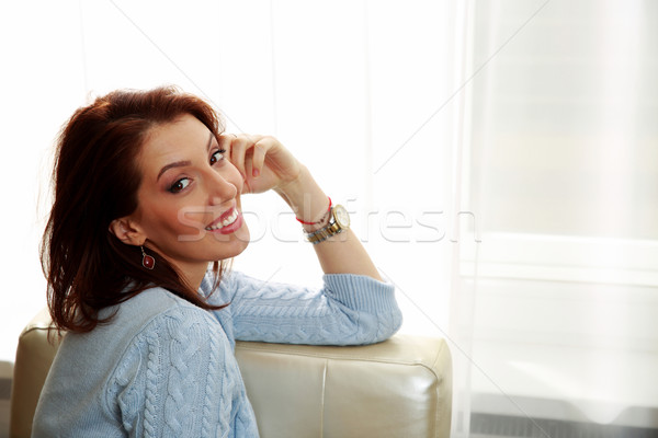 Happy woman sitting on the sofa at home Stock photo © deandrobot