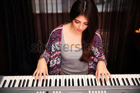 Young beautiful woman playing on piano at home Stock photo © deandrobot