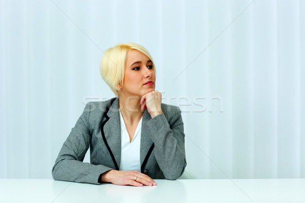 Beutiful thoughtful businesswoman sitting at the table and looking left at copyspace in office Stock photo © deandrobot