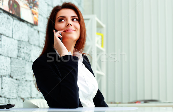 Young happy businesswoman talking on the phone and looking away at copyspace in office Stock photo © deandrobot