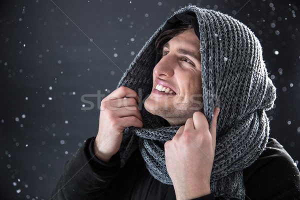 Happy handsome man with snow on background. Winter coming Stock photo © deandrobot