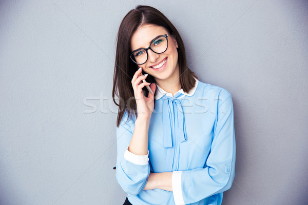 Happy businesswoman talking on the phone Stock photo © deandrobot