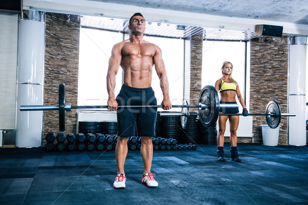 Muscular man and woman workout with barbell Stock photo © deandrobot