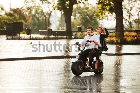 Cheerful young couple riding a scooter  Stock photo © deandrobot