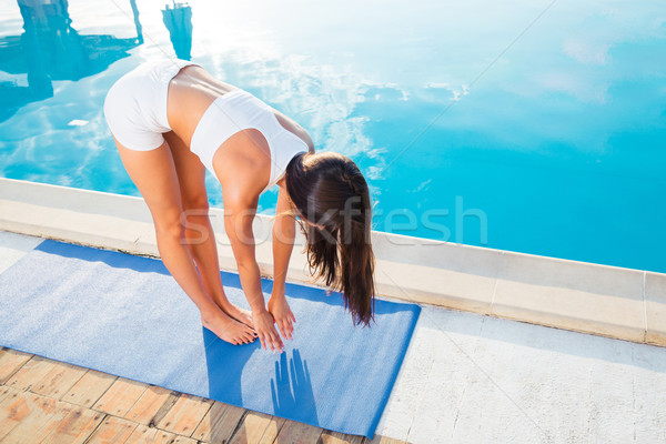 Woman doing yoga exercises on mat Stock photo © deandrobot