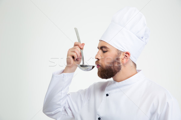Chef cook holding a soup ladle and smelling it Stock photo © deandrobot