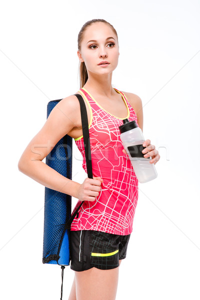 Young sportswoman with yoga mat and bottle of water Stock photo © deandrobot